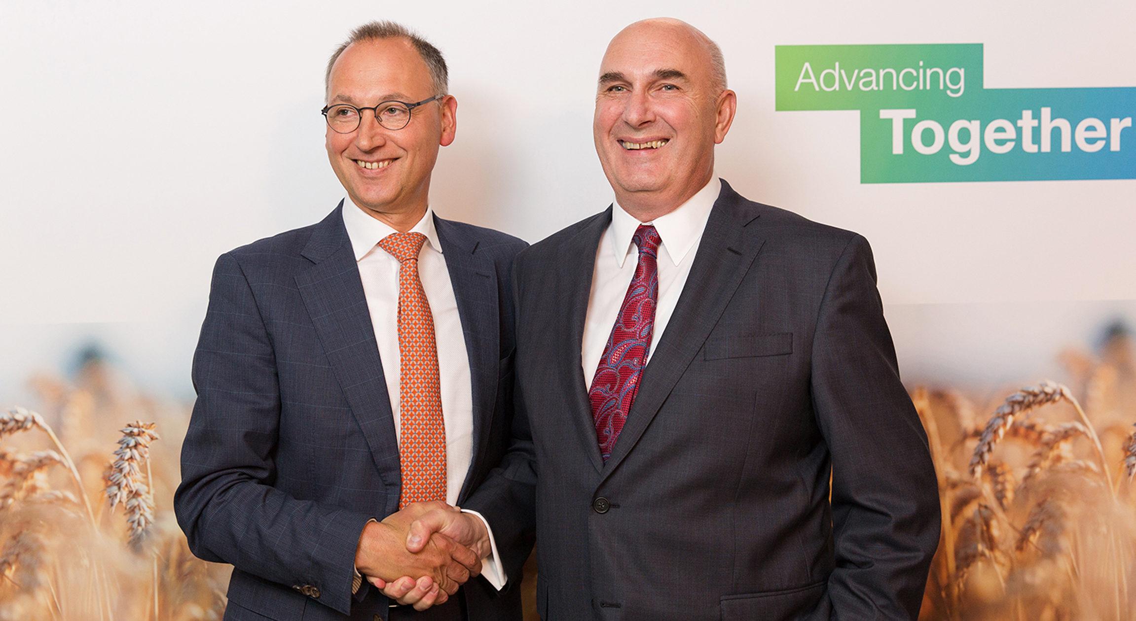 Werner Baumann, presidente executivo da Bayer (à esquerda) aperta a mão de Hugh Grant, presidente da Monsanto.