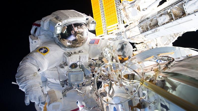 Como parte da sua missão de bater o recorde, o astronauta Jeff Williams instalou um novo adaptador de docking na Estação Espacial Internacional durante uma caminhada especial de seis horas. (ESQUERDA) FOTOGRAFIA DA NASA