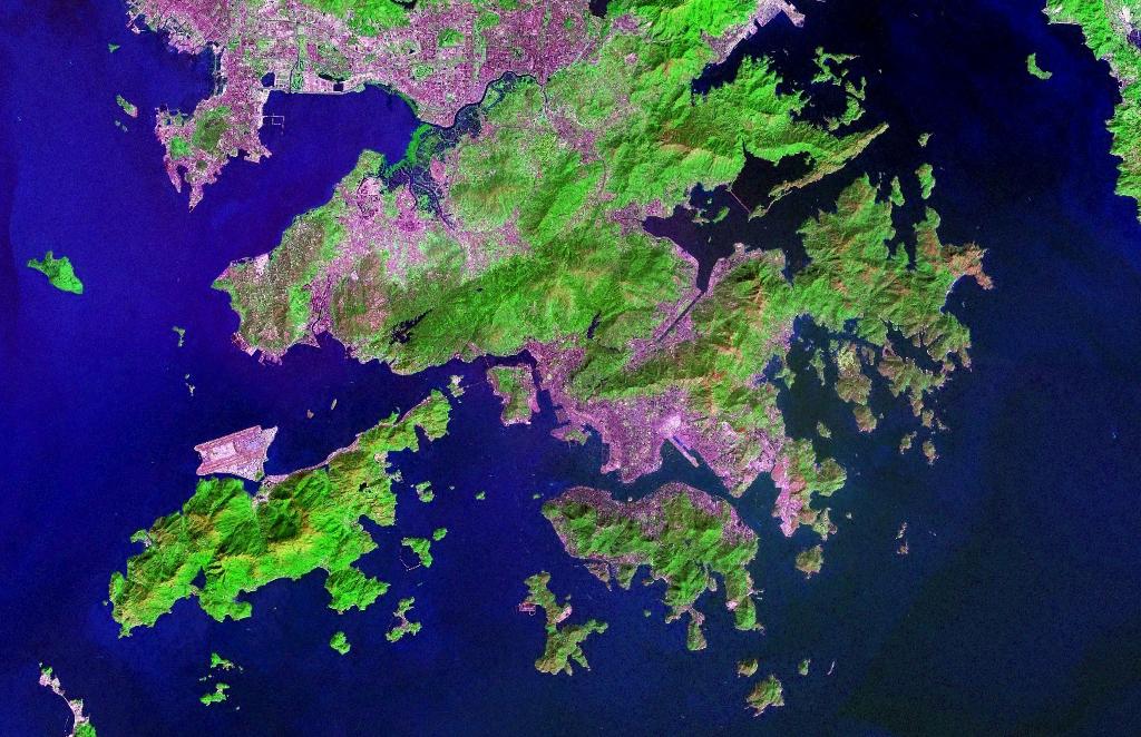 Esta imagem de satélite da NASA, com cor falsa, permite ver as zonas urbanas de Hong Kpmh e da península de Kowloon, relativamente às zonas de vegetação.